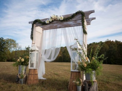 Outdoor wedding arbor with toile and ceremonial field created by Sheila Keeler